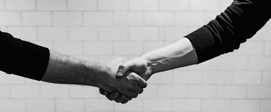 event-akademie.at I Foto in schwarz/weiß, das zwei Personen zeigt, die Hände schütteln.